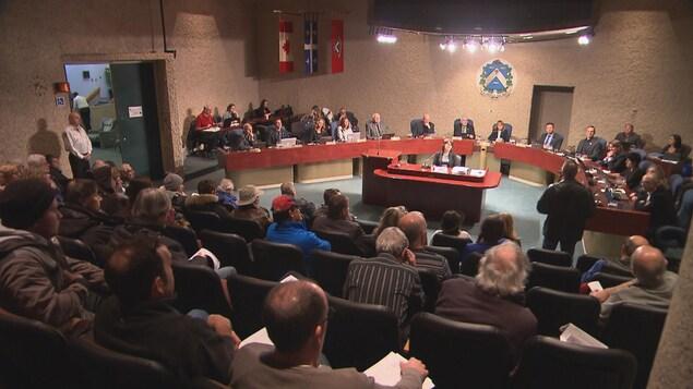 Citoyens dans la salle du conseil assis, un debout face aux conseillers
