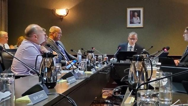 Des hommes assis autour d'une table en réunion