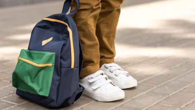 Des chaussures blanches d'enfants, avec un sac à dos à côté.