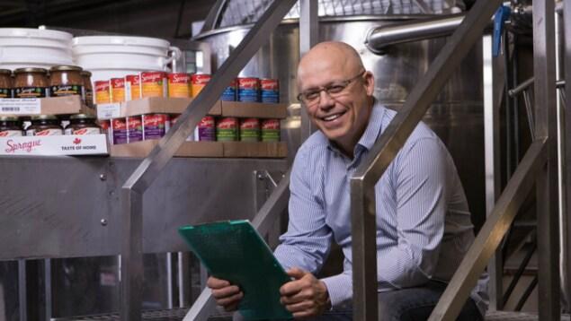 Rick Sprague est assis sur un escalier en métal dans son usine.