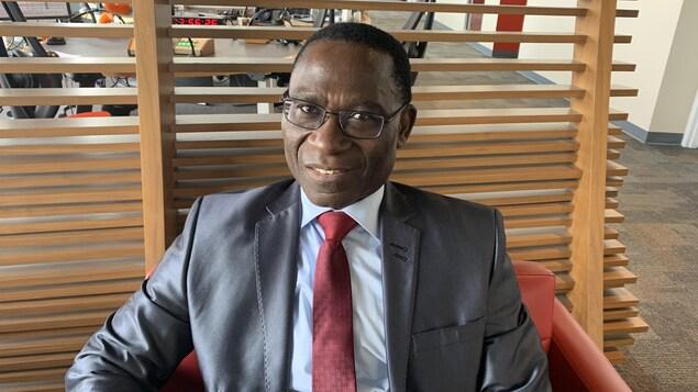Un homme qui porte une veste grise et une cravate rouge