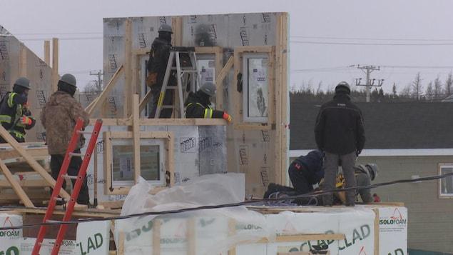 Sept personnes construisent une maison.