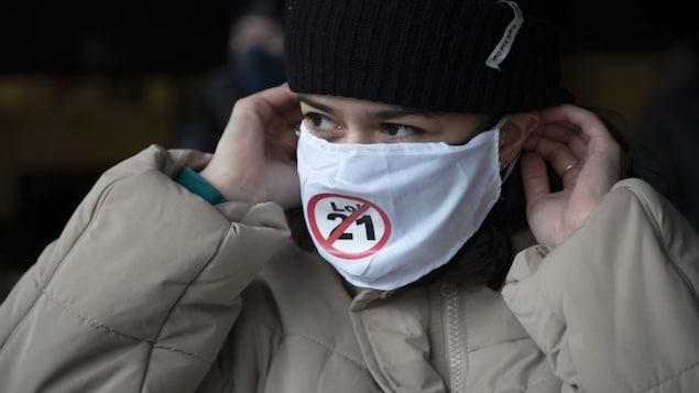 Une femme avec un masque noir sur lequel apparaît un écusson qui rejette la loi 21.