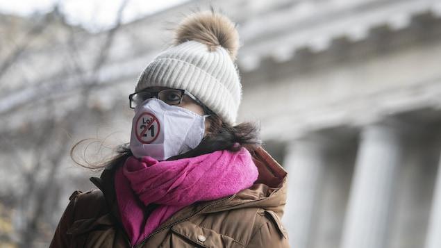 Une femme porte un masque sur lequel est imprimé un symbole contre la loi 21.