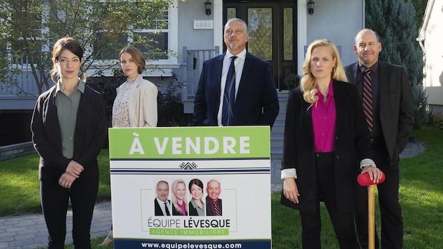 Les cinq personnes se tiennent en rangée, à distance, derrière une affiche de vente immobilière, sur le terrain gazonné devant une maison.