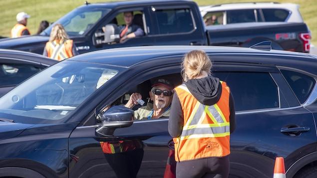 Un homme âgé assis au volant de sa voiture montre une pièce d'identité à une femme debout à côté du véhicule, portant une veste orange.