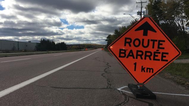 Un panneau « route barrée » prévient d'un éventuel barrage à 1 kilomètre.