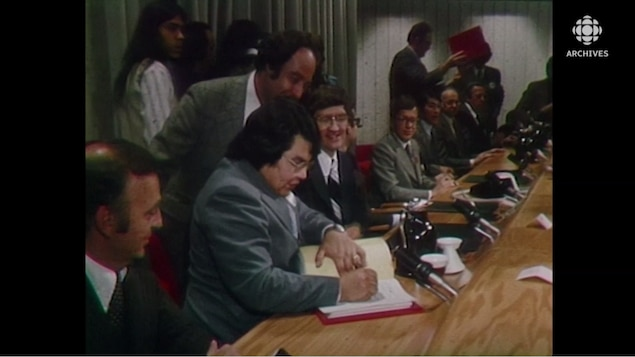 Homme qui signe un document sous le regard des autres hommes assis près de lui.