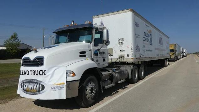 Plusieurs semi-remorques roulent à la queue leu leu sur l'autoroute périphérique de Winnipeg.