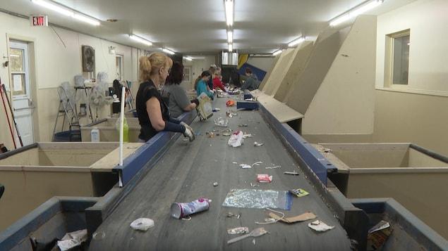 Des employés sont à l'œuvre au centre de tri de matières recyclables.