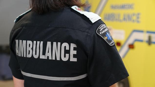 Une femme porte une chemise sur laquelle se trouve un écusson portant l'inscription « Technicien ambulancier - Paramédic - Québec ».
