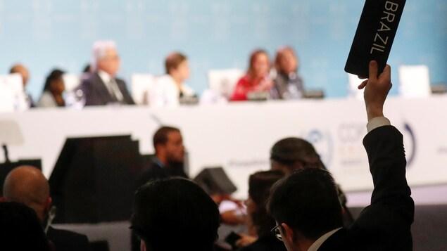 Lors des discussions, un délégué du Brésil lève sa main avec une pancarte où est inscrit le nom de son pays.
