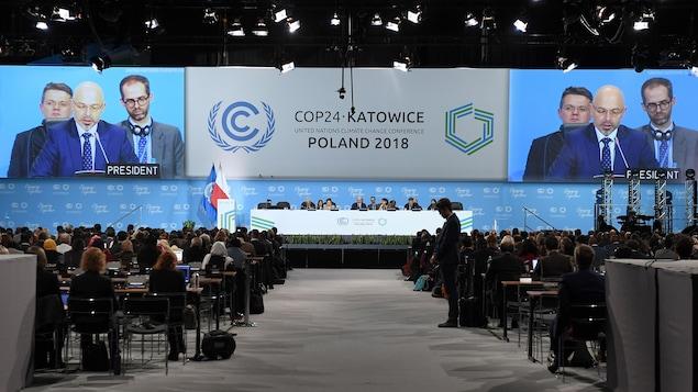 D'énormes écrans diffusent le discours d'un homme assis à une longue table sur une estrade à l'intérieur d'un stade où sont réunis plusieurs diplomates en Pologne.