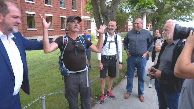 Le député Harold Lebel pose sa main sur l'épaule de Patrice Coquereau, pendant que le maire de Rimouski, Marc Parent, le député Guy Caron et des curieux regardent le comédien qui s'exprime devant une caméra.