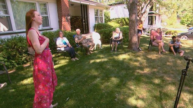 Une chanteuse offre un concert dehors chez des particuliers.