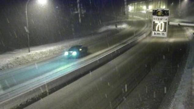 Une voiture roule sur l'autoroute enneigée alors qu'un panneau signale que la vitesse est limitée à 70 kilomètres par heure.