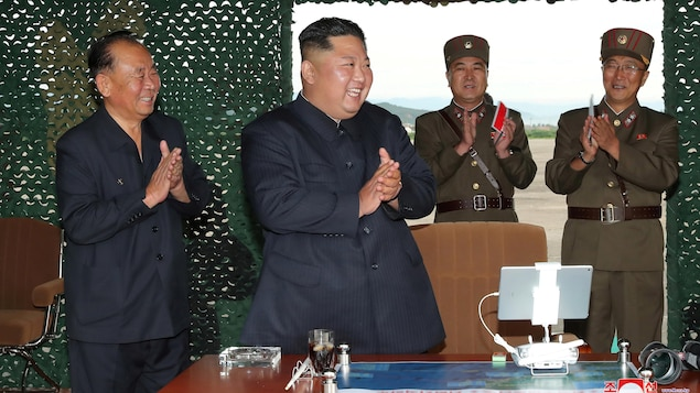 Kim Jong-un applaudi, entouré de généraux.