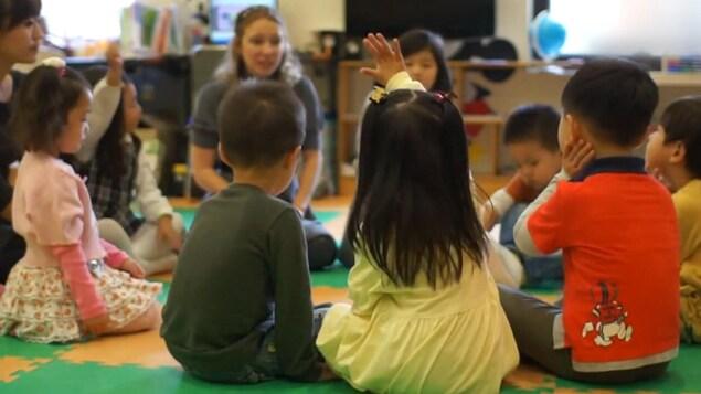 Des enfants à la maternelle sont assis en rond.