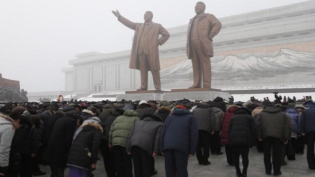 Les Nord-Coréens saluent deux statues de bronze représentant d'anciens leaders du pays Kim Il Sung et Kim Jong-il.