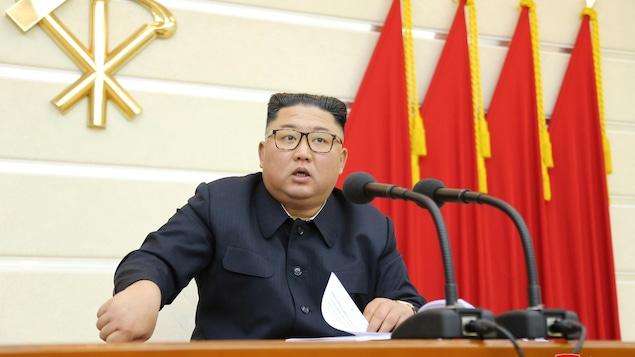 Le leader nord-coréen Kim Jong-un assis derrière une table et des micros, des drapeaux rouges derrière lui, à Pyongyang vendredi.