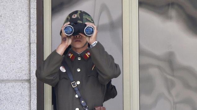 Un soldat nord-coréen regarde dans des jumelles.