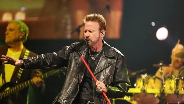 Corey Hart sur scène devant un micro. Il porte un veston de cuir et tient son micro sur pied.