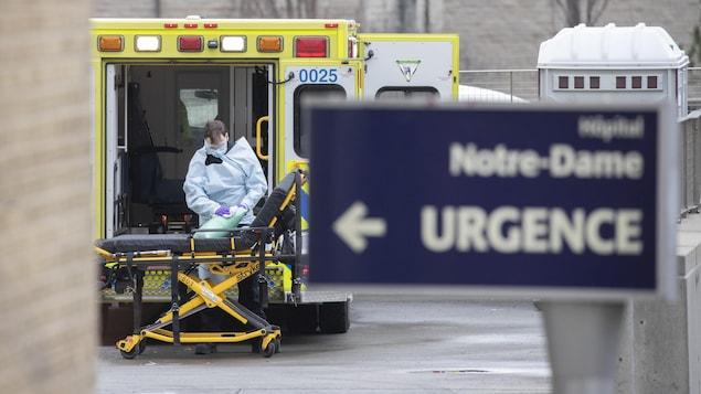 Un homme en habit de protection nettoie un coussin près d'une ambulance à l'urgence de l'Hôpital Notre-Dame, à Montréal.