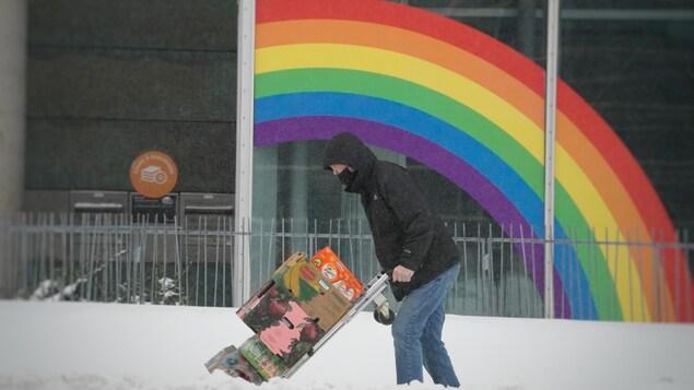 Un homme dehors transporte des boîtes devant un établissement sur lequel est collé un grand arc-en-ciel.
