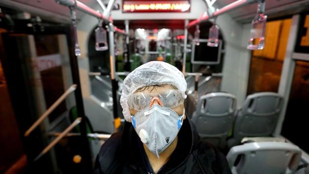 Une femme masquée et portant des lunettes de sécurité et un bonnet est debout au milieu d'un autobus.