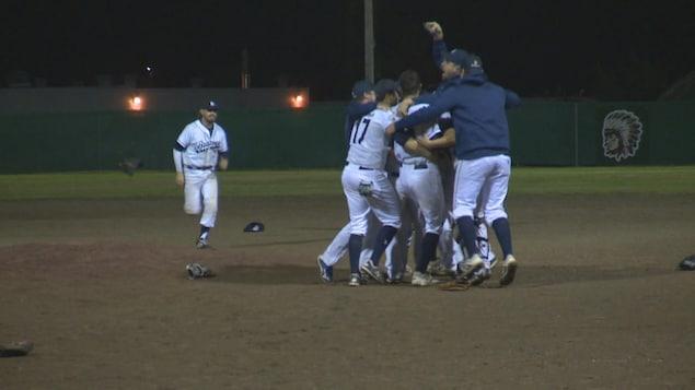 Des joueurs de baseball s'enlacent sur le terrain après une victoire.