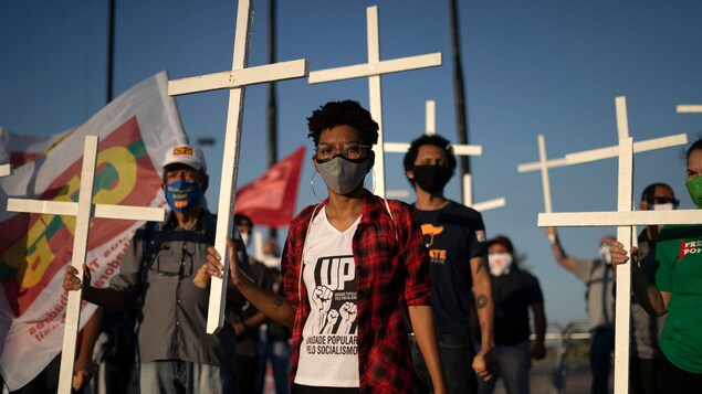 Plusieurs personnes avec des masques tiennent des croix blanches dans une main.