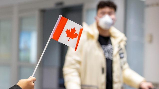 Une main agite un petit drapeau du Canada alors qu'un homme portant un masque marche dans l'aéroport.