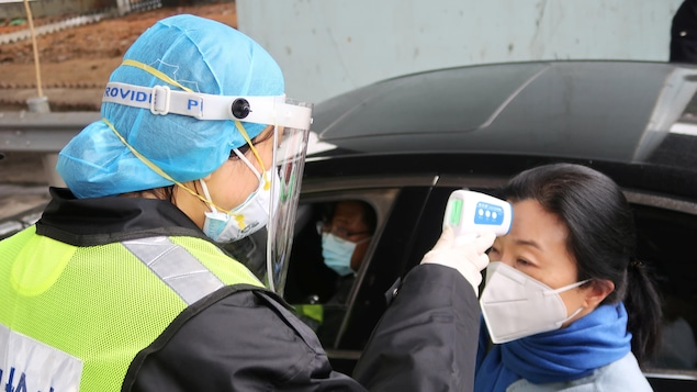 Une femme avec un masque prend la température d'une femme avec un thermomètre qu'elle pointe sur son front.