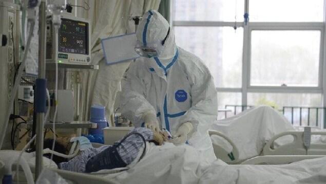 Un soignant portant une tenue de protection est penché sur le lit d'un patient.