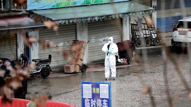 Un homme en tenue de protection au milieu du marché.