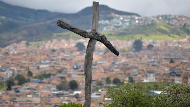 Une croix en bois en avant-plan et la ville au fond.