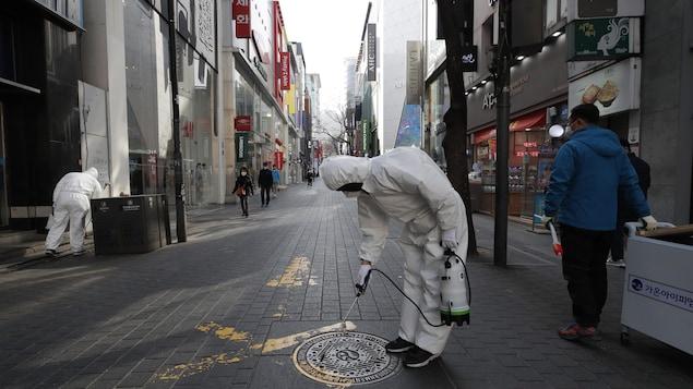 Des employés mènent une opération de désinfection dans un quartier commerçant de Séoul, en Corée du Sud.