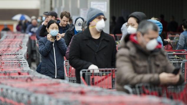 Une file de personnes portant un masque attendant avec leur panier d'épicerie.