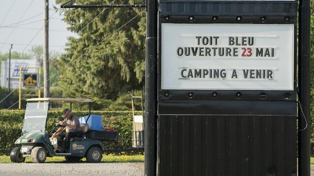 Une homme dans une voiturette sur un terrain de camping.