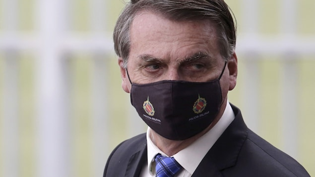 Jair Bolsonaro porte un masque noir.