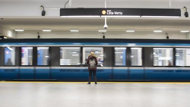 Une rame de métro de la ligne orange, déserte, vide. Seule une utilisatrice, de dos, attend de monter.