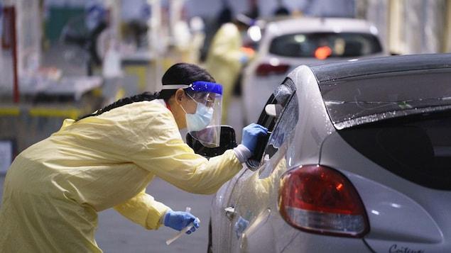 L'infirmière insère une tige dans la bouche de la personne qui attend dans sa voiture.