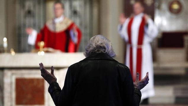 Un fidèle a les deux bras ouverts et écoute le célébrant.