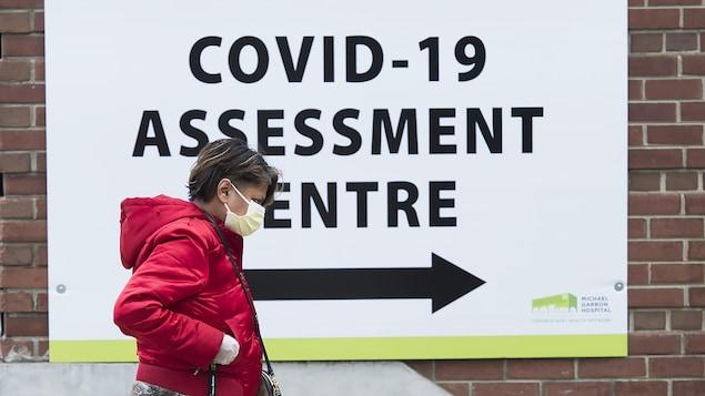 Une femme portant un masque devant un centre de dépistage à Toronto.