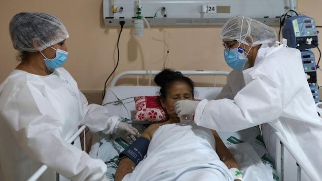Deux infirmières donnent un verre d'eau à une femme alitée.