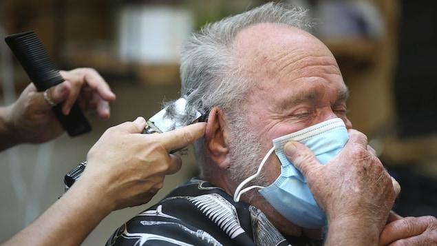 Un homme se fait couper les cheveux en tenant un masque sur son visage.