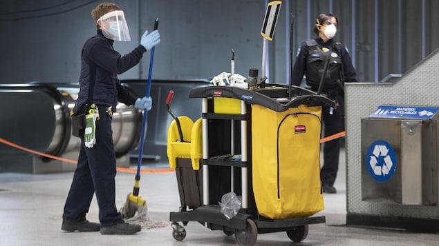 Un employé d'entretien nettoie le plancher à la station Berri-UQAM.