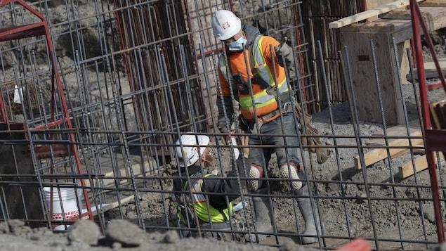 Deux hommes portant des masques se parlent sur un chantier de construction.