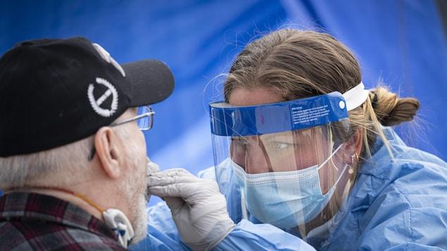 Une professionnelle de la santé effectue un test de dépistage de la COVID-19 sur un patient âgé.
