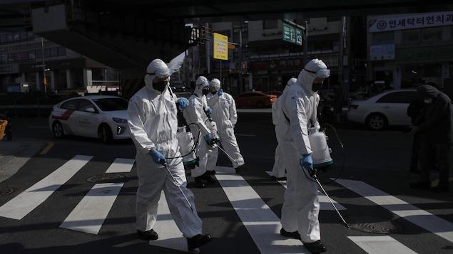 Des soldats envoient du désinfectant dans les rues en Corée du Sud. Ils sont habillés de blanc et portent des masques.